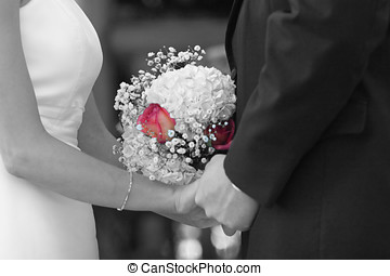 Taking vows. - Bride and groom holding hands during their...