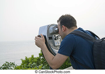 Coin Operated Binoculars - A young man looks through some...