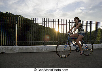 Girl Riding a Bike - A young woman riding a bicycle across...