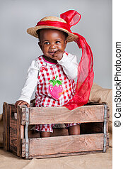 Friendly, but busy! - A small African girl dressed as a farm...