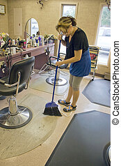 Hairdresser Sweeping - A hairdresser working in the salon...