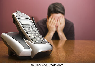 Man hides his face waiting for the phone to ring - A man...