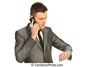 Stressed business man by phone mobile looking to wristwatch...