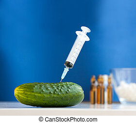 Cucumber with syringe. Bio genetics research of food against...