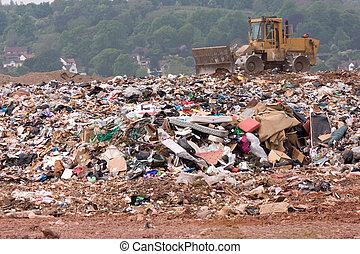 Bulldozer on a landfill site - A bulldozer moving garbage on...