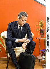 Bureau - Businessman checking his watch while waiting