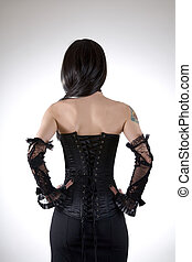 Rear view of a woman in black corset and skirt, studio shot