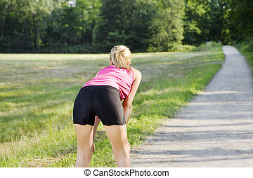 jogging - Rear view of young woman resting on pathway Copy...