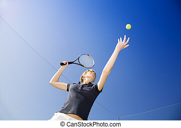 tennis - blond woman playing tennis, about to hit the ball...