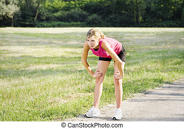jogging - Young blond woman taking breath after jogging