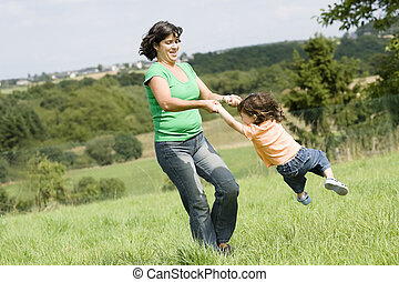 Mother is playing with her daughter in a farmers field