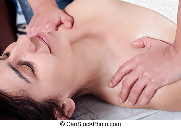 antistress - osteopathy procedure in a shoulder of a young...