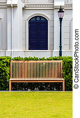 Wooden Bench in front of White Building and Street Lamp