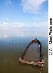 Lonelyness - Old boat under water under bright sky