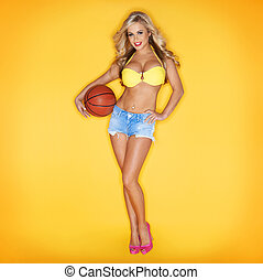 Sexy Blonde Woman Holding Basketball In Hand On Yellow...