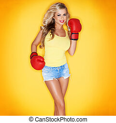 Beautiful Blonde Woman Wearing Boxing Gloves On Yellow...