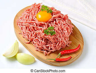 Raw minced meat and other ingredients on cutting board