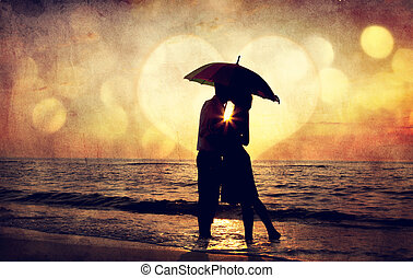 Couple kissing under umbrella at the beach in sunset Photo...