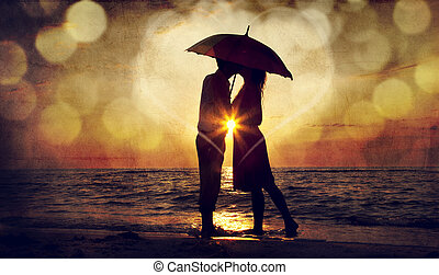 Couple kissing under umbrella at the beach in sunset. Photo...