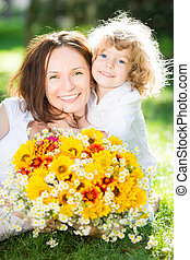 Mother`s day - Happy child and woman with bouquet of spring...
