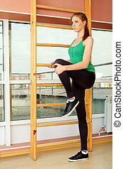 foot exercise - Young sporty woman doing exercises in the...