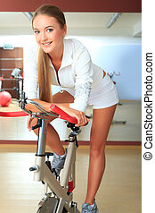 white uniform - Young sporty woman doing exercise on bicycle...