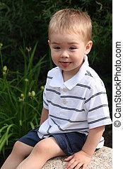 Boy Sitting on Rock - A toddler boy wearing a striped golf...