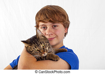 cute boy hugging his cat in the arm