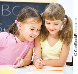 Little girls are writing using a pen - Cute little girls are...