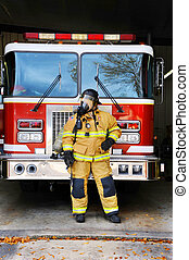 Beside Firetruck - Woman firefighter stands in front of fire...