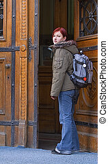 Back to school - Young redheaded student opening the...