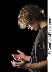 Young man in prayer with cupped hands - A young man in...