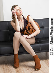 woman wearing fashionable brown shoes with a handbag sitting on sofa