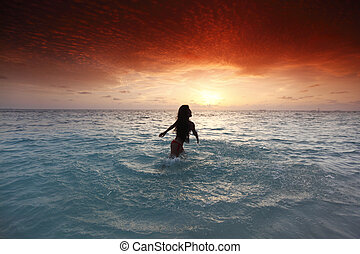 Woman splashing in sea on sunset