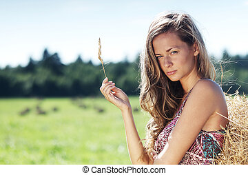 girl next to a stack of hay - portrait of a girl next to a...