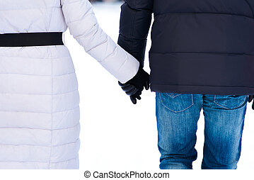 Rear view of couple holding hands and walking on the bright...