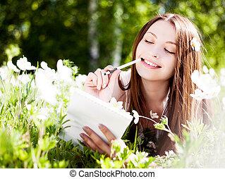 woman outdoors - beautiful young brunette woman writing in...