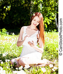 woman outdoors - beautiful young woman writing in her diary...