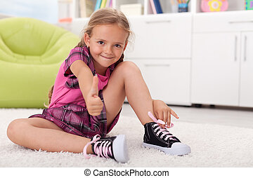 Little girl learning how to tie her shoes, being proud of...