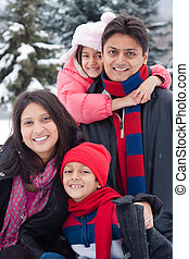 East Indian family playing in the snow