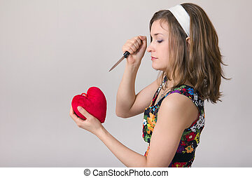 woman cutting a heart toy with a knife