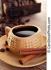 Cup of coffee with coffee beans and cinnamon bars