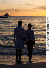 romantic young couple sunset silhouette on beach. honeymoon