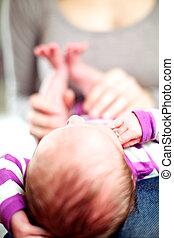 Tiny baby lying with its head towards the camera