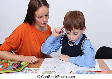 mother or teacher helping kid with schoolwork