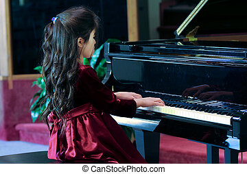 Child playing grand piano in formal - Child playing grand...