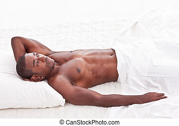 resting ethnic black Afro-American man in bed