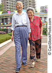 an intimate senior couple are walking