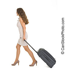 Young woman walking with wheels suitcase Side view