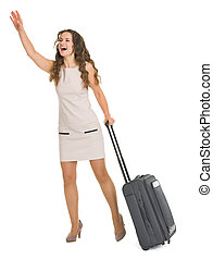 Young woman with wheels suitcase catching taxi